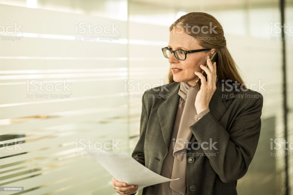 Mature businesswoman on phone standing in an office stock photo