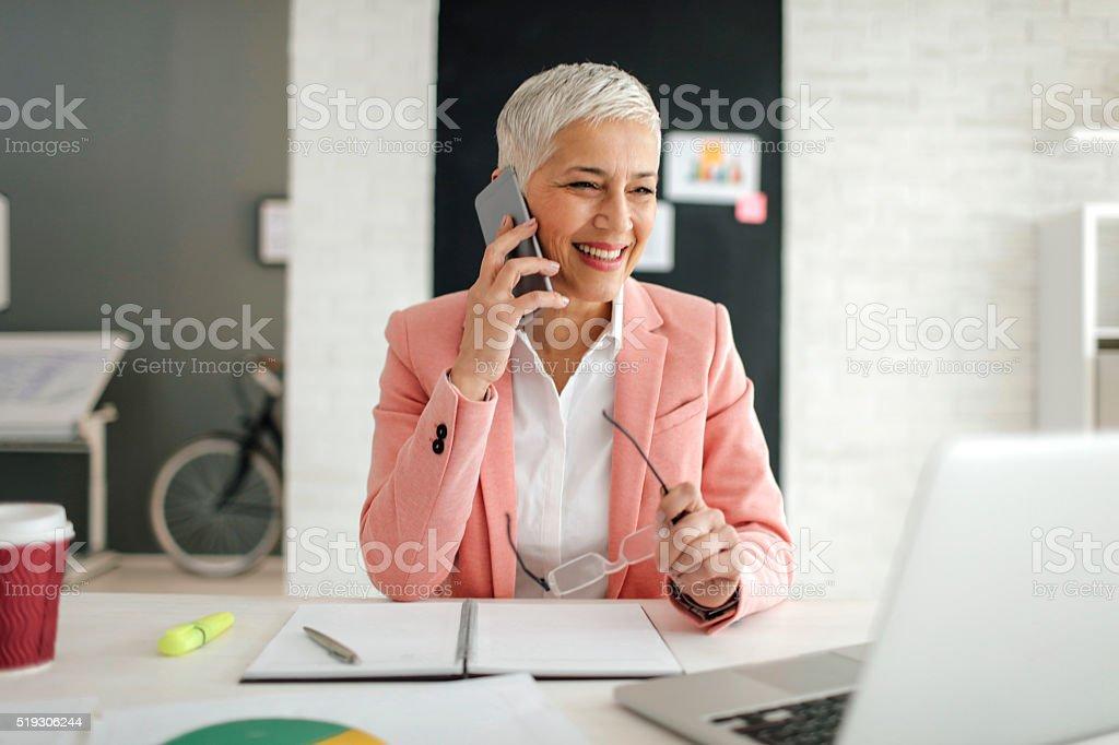 Mature femme d'affaires au téléphone à son bureau. - Photo