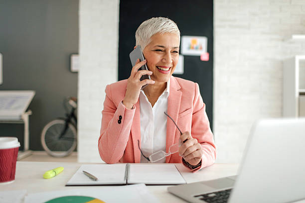 mature businesswoman on the phone in her office. - older woman phone stock photos and pictures