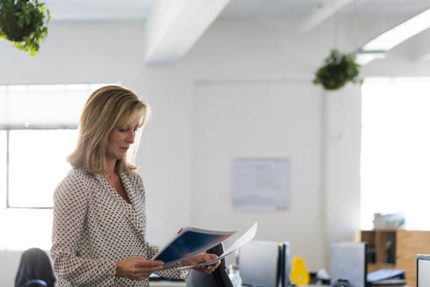 Mature businesswoman reading documents in office stock photo