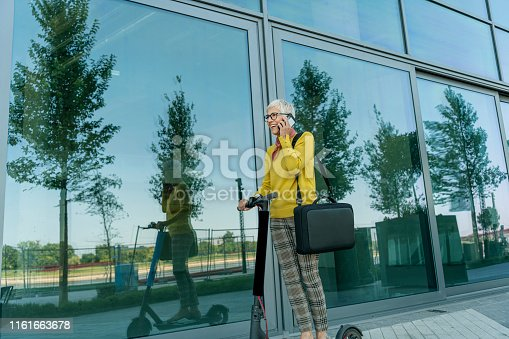 874772840istockphoto Mature Businesswoman riding a electric scooter  in the city 1161663678