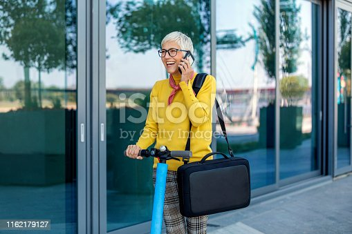 874772840istockphoto Mature Businesswoman riding a electric scooter  in the city 1162179127