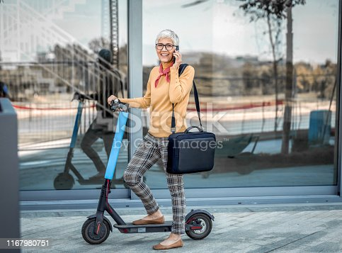 874772840istockphoto Mature Businesswoman riding a electric scooter  in the city 1167980751