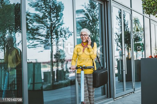 874772840istockphoto Mature Businesswoman riding a electric scooter  in the city 1170140709