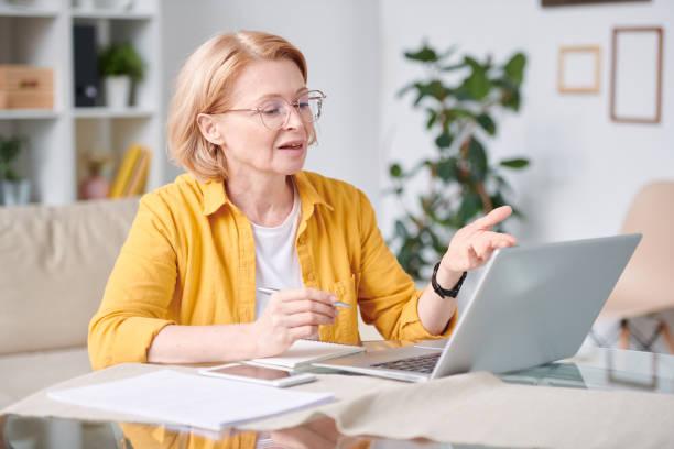 Reife Geschäftsfrau sitzt am Schreibtisch vor dem Laptop, während Sie Video-Chat verwenden – Foto