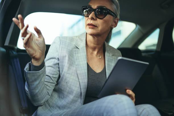 mature businesswoman sitting on back seat of a car - senior business woman tablet imagens e fotografias de stock