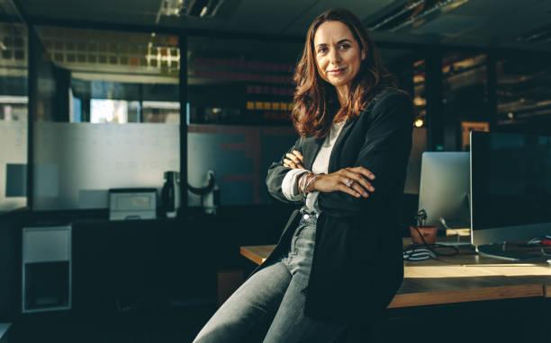 Mature businesswoman sitting on her desk stock photo