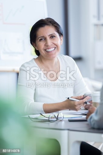 1150572102istockphoto Mature businesswoman smiles for camera at work 831814978