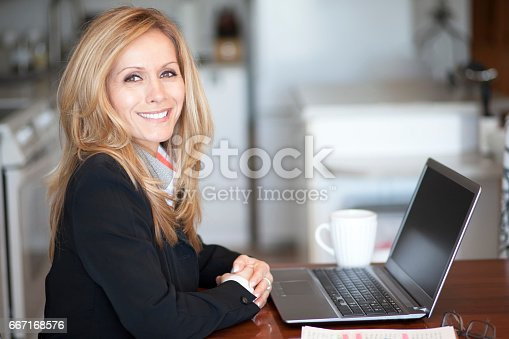 625010932istockphoto Mature Businesswoman Smiling At The Camera. Working At Home. 667168576