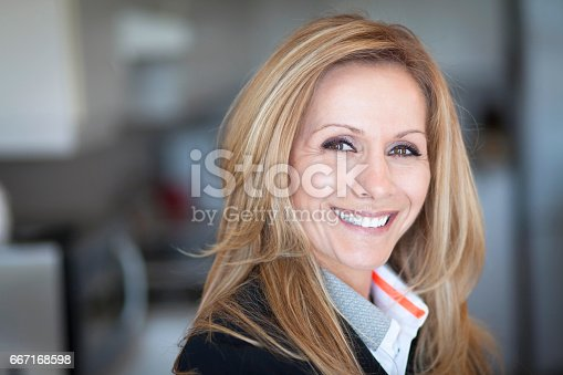 625010932istockphoto Mature Businesswoman Smiling At The Camera. Working At Home. 667168598