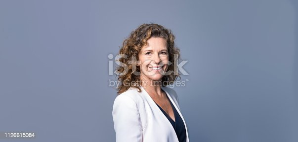 istock Mature businesswoman smiling on bluegray background 1126615084