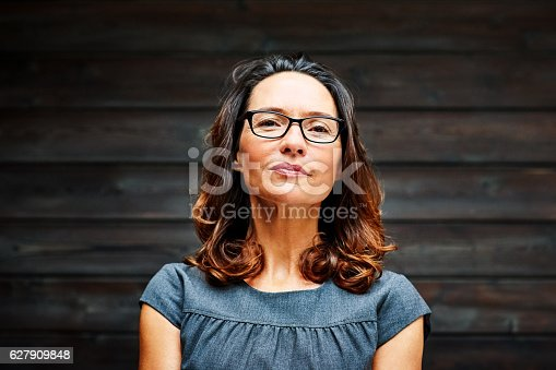 istock Mature businesswoman standing against a wooden wall in office 627909848