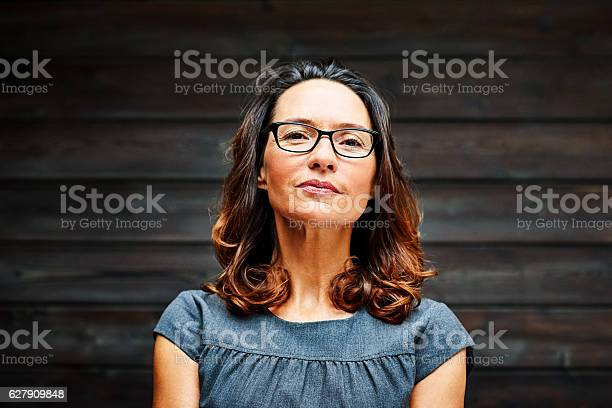 Mature businesswoman standing against a wooden wall in office picture id627909848?b=1&k=6&m=627909848&s=612x612&h=yqz ygjwz2mvnv5fxmk9vxost iq  esjtkgrg1wgmk=