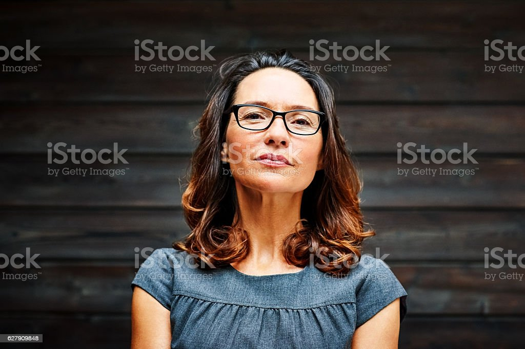 Mature businesswoman standing against a wooden wall in office stock photo