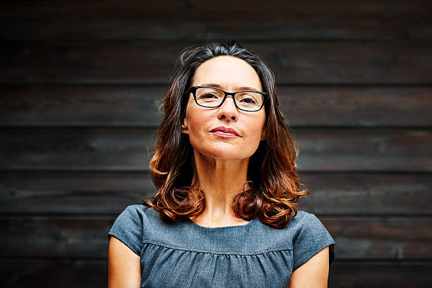 Mature businesswoman standing against a wooden wall in office - Photo