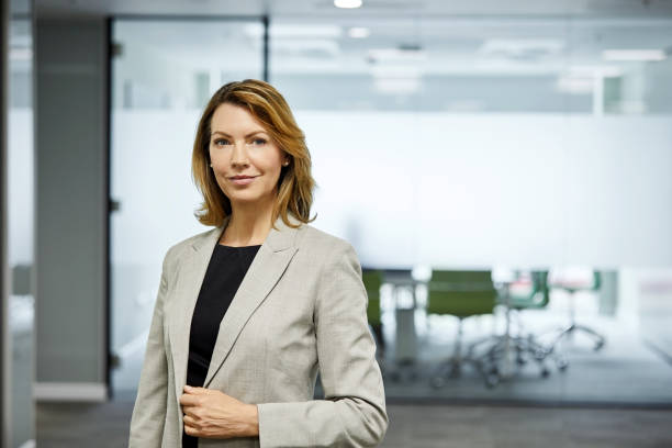 Mature businesswoman standing against board room stock photo