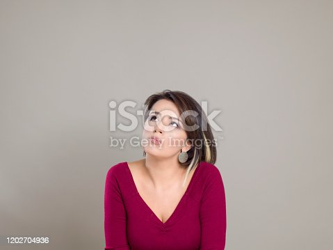 Mature businesswoman thinking while looking up against gray background