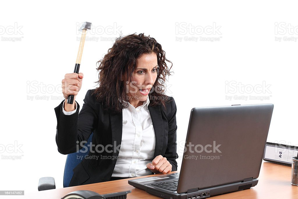 Mature businesswoman trying to destroy a laptop with hammer royalty-free stock photo