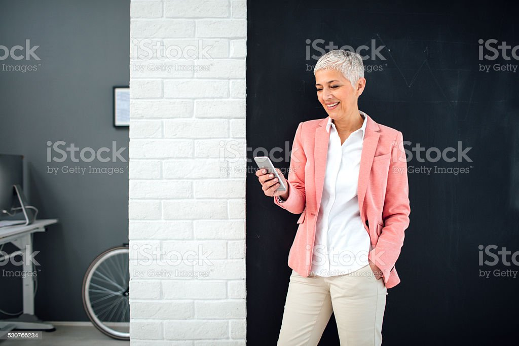 Mature Businesswoman Using Smart Phone In Her Office. stock photo