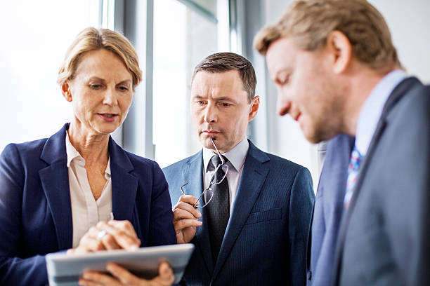 mature businesswoman viewing proposal to colleagues - senior business woman tablet imagens e fotografias de stock
