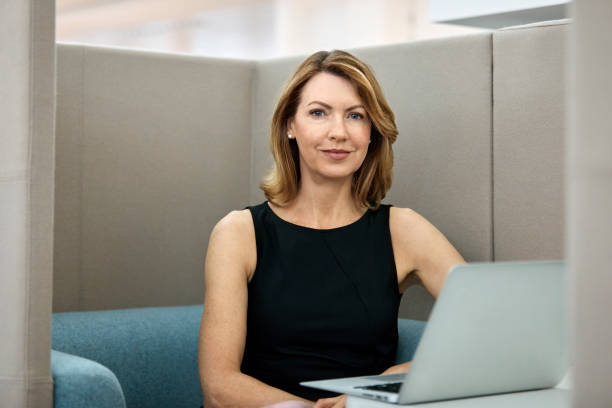 Mature businesswoman with laptop in office Mature businesswoman with laptop in office. Confident executive is smiling at workplace. Female professional is wearing smart casuals. medium length hair stock pictures, royalty-free photos & images