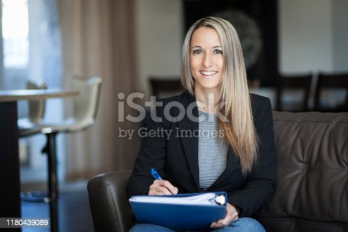 464696188istockphoto Mature Businesswoman Working At Home. Smiling 1180439089