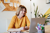 istock Mature businesswoman working from home and attending video conference meeting 1255011308