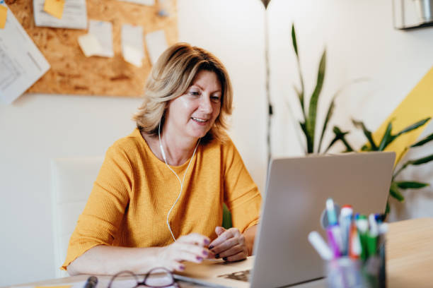 Mature businesswoman working from home and attending video conference meeting stock photo