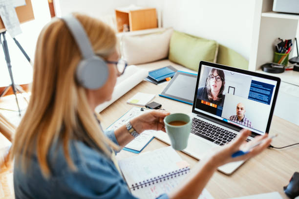 Mature businesswoman working from home during pandemic and attending video call meeting stock photo