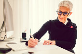 Mature businesswoman working in her home office. Sitting by the desk and taking notes.