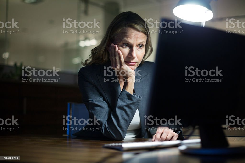 Mature businesswoman working late in office stock photo