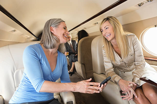 Mature businesswomen talking while on board private corporate jet stock photo