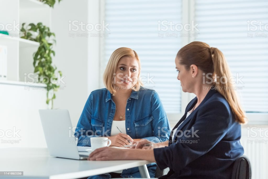 Mature businesswomen talking while sitting at desk Businesswomen talking while sitting at desk. Female expertise are discussing new business plans. They are sitting in office. 40-44 Years Stock Photo