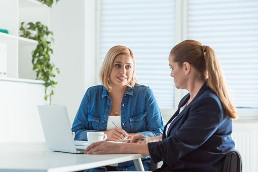 Mature Businesswomen Talking While Sitting At Desk Stock Photo - Download Image Now