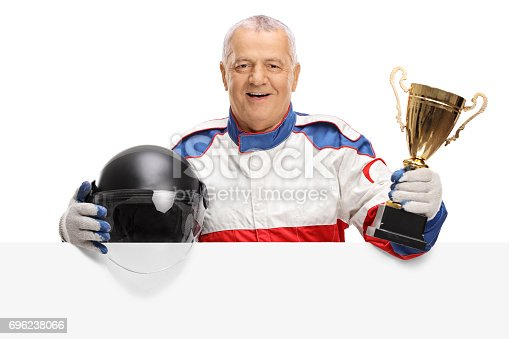 istock Mature car racer with golden trophy and helmet behind panel 696238066