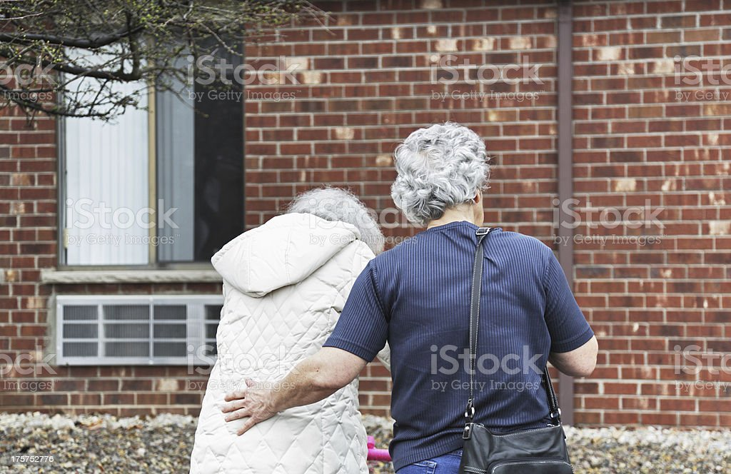 Mature Caregiver Daughter Supporting Elderly Mother royalty-free stock photo