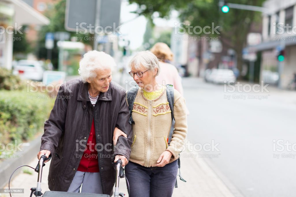 mature caregiver supporting senior woman walking in the street stock photo
