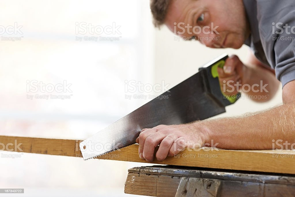 Mature carpenter cutting wooden plank with a saw royalty-free stock photo
