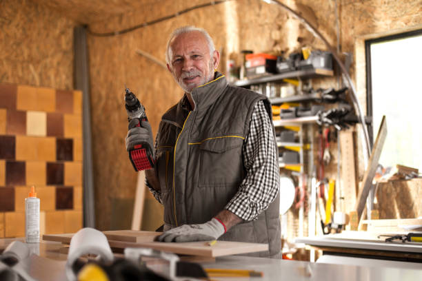 Mature carpenter in workshop holding cordless drill stock photo