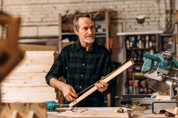 Mature carpenter measuring a length of wooden plank in workshop stock photo