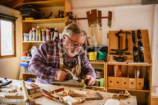 Man in his 50s using plane to shape timber in studio, small business owner, self employment, craft, carpentry