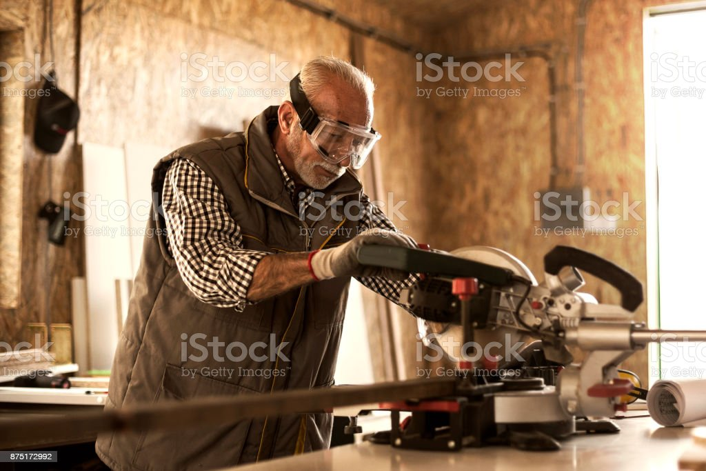 Mature carpenter using circular saw stock photo