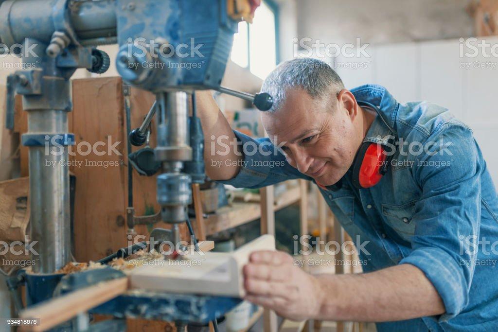 성숙한 카펜터 사용하여 드릴 워크숍입니다 누르십시오 - 로열티 프리 50-59세 스톡 사진