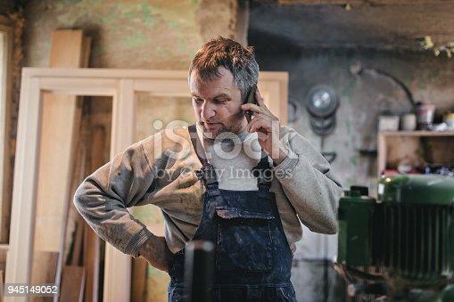 Mature carpenter using phone in the workshop