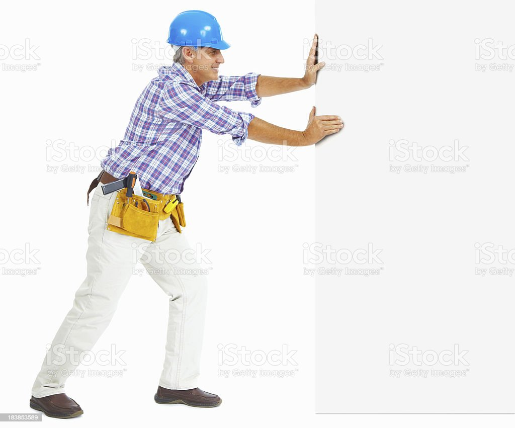 Mature carpenter with tool belt pushing wall - white background royalty-free stock photo