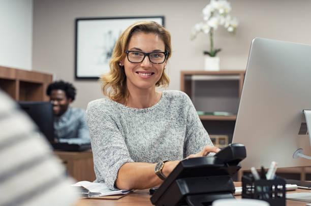madura mujer casual, trabajando en equipo - recepcionista fotografías e imágenes de stock