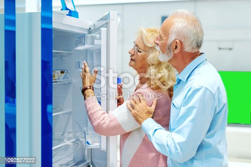 876810414istockphoto Mature Caucasian couple choosing fridge while standing in tech store. 1092527222