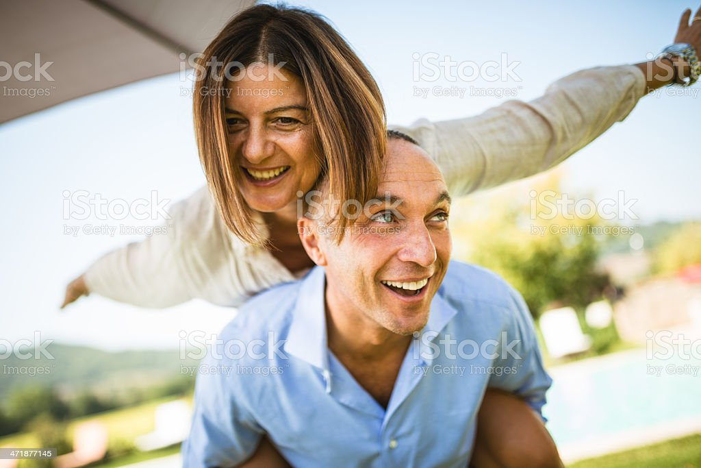mature caucasian couple embracing in front of own house royalty-free stock photo