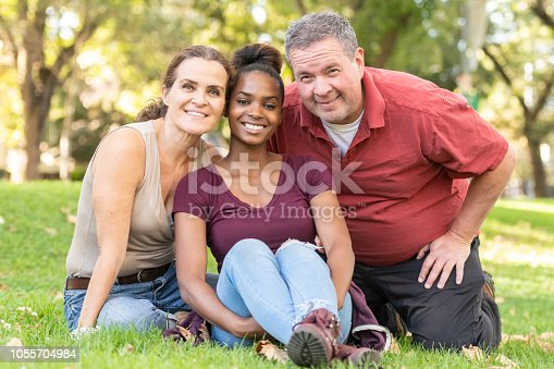 Smiling mature caucasian couple posing with their black adopted daughter sittinng on the grass at a public park