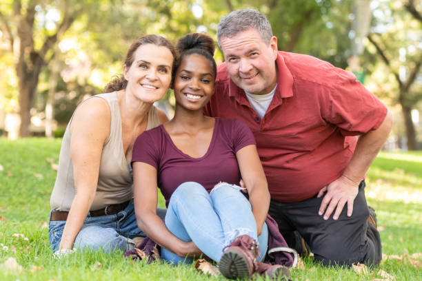 Mature caucasian couple posing with their black adopted daughter stock photo